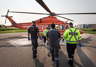 two Ornge paramedics boarding an Ornge helicopter