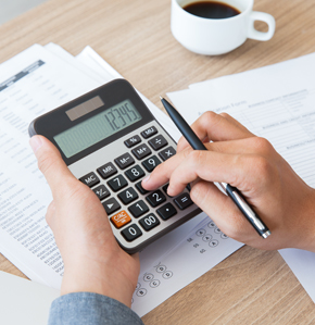A hand holding a calculator over a sheet with financial information