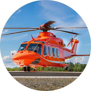 An Ornge Leonardo AW139 helicopter on a helipad with a blue sky in the background