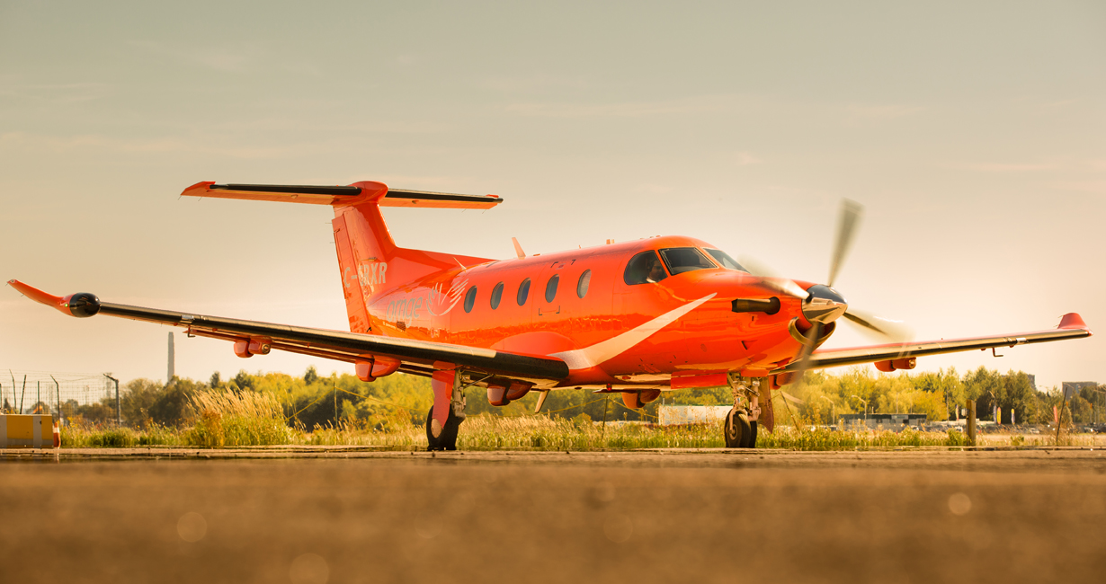 An Ornge Pilatus PC-12 airplane in front of an beautiful orange sunset sky