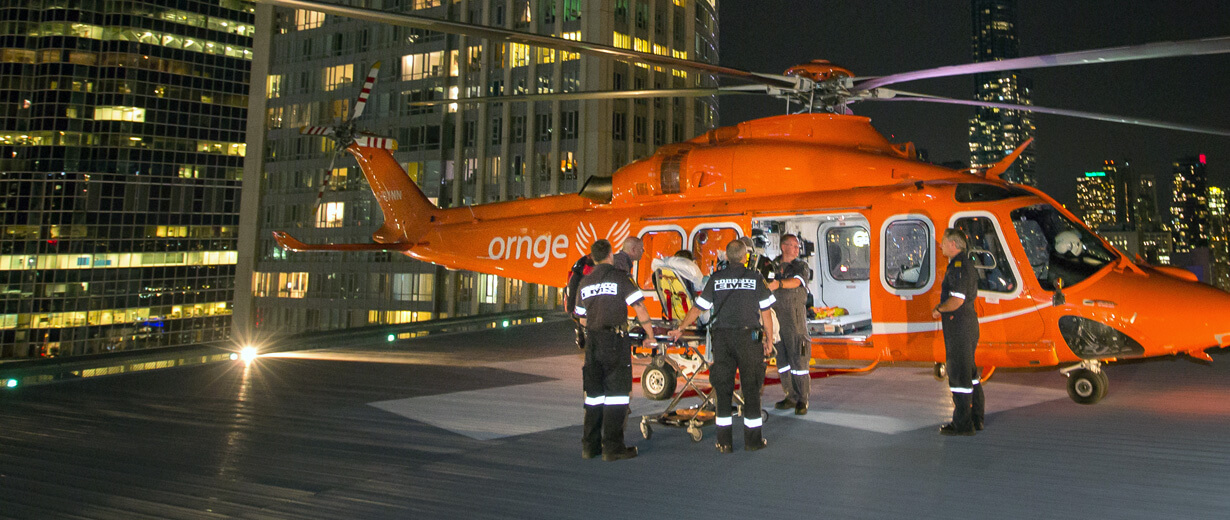 A group of Ornge paramedics bring a patient on a gurney into a helicopter at night