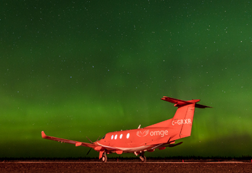 An image of an Ornge helicopter landed at night