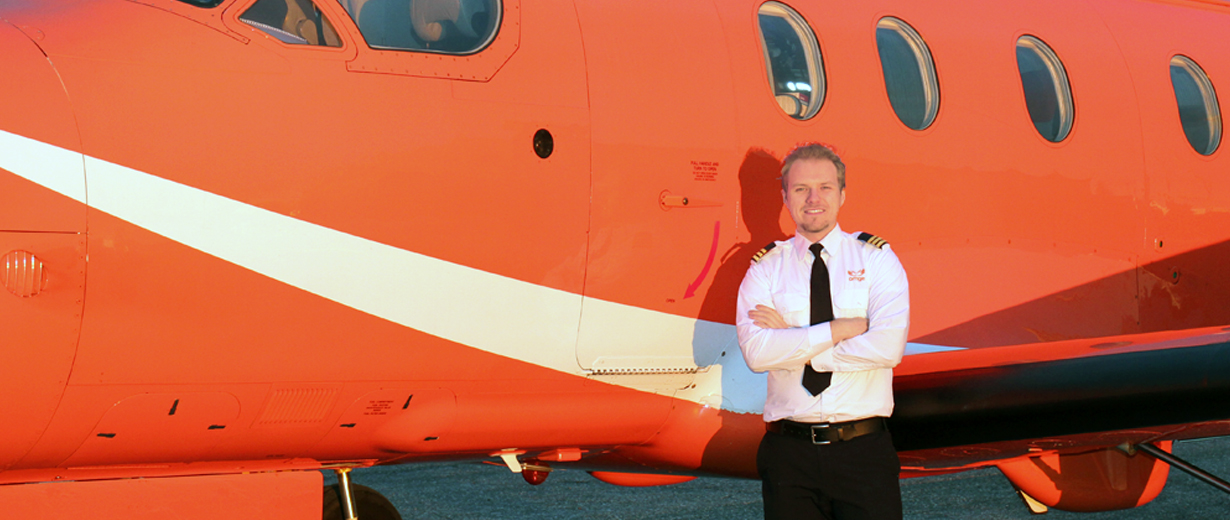 A picture of First Officer Dominik Ochmanek standing beside an Ornge Plane
