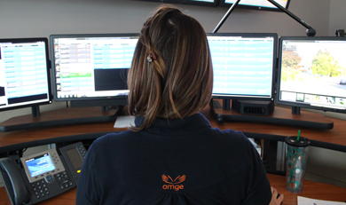 a photo of a female Communications Officer sitting in front of several computer screens